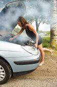 Постер, плакат: Сюда приходит молодая женщина склонившись над ветром двигатель ее автомобиля глядя на нефть тогда как дым