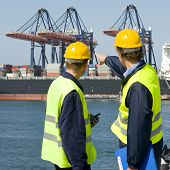Two dockers in discussion, pointing at the unloading operations of a huge container ship