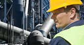 foto of retarded  - Stern looking worker in front of an imposing factory of a heavy industry facility - JPG