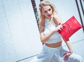 Glamorous Female Fashion Model Wearing Casual Elegant Outfit White Crop Top. Blonde Woman Holding Re poster