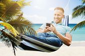 Happy Young Man Relaxing In Hammock Using Smartphone poster