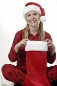 Woman Looking Into Her Stocking On Christmas Morning poster