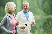 Active senior man with bottle of water looking at his wife while jogging in the morning poster