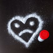 Salt Scattered On Black Surface. Drawn Heart With A Sad Face. Concept- Diet, Harm To Health From Exc poster