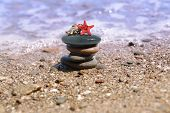 stock photo of sand lilies  - sea still life with seastar and stacked pebbles - JPG