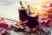 Glass Mugs Of Mulled Wine With Spices And Orange Citrus Fruits On Wooden Table With Fallen Maple Lea poster