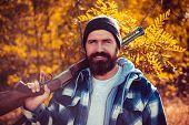 Bearded Hunter Man Holding Gun And Walking In Forest. Hunter With Shotgun Gun On Hunt. Autumn Huntin poster