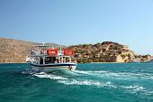 A pleasure boat takes day-trippers to Spinalonga island fortress, Crete - a Venetian castle that bec
