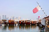A view of the dhows in Doha harbour, with the Qatari flag flying from them and the new city skyline