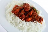 A plate with chicken tikka masala on a bed of white basmati rice, on a plate, photographed at an ang