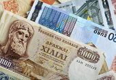 A mixture of old Greek drachma banknotes and euro notes that succeeded them. Greece's adoption of th