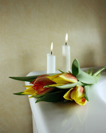 foto of funeral  - Beautiful tulips in red and yellow with candles behind for wedding or funeral - JPG