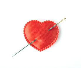 stock photo of broken heart  - Red satin heart pierced with a sewing needle - JPG