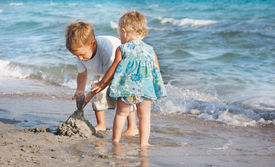 picture of children playing  - two children playing on sand beach - JPG