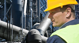 pic of retarded  - Stern looking worker in front of an imposing factory of a heavy industry facility - JPG