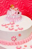stock photo of christening  - Closeup view of white christening cake for girl with topper and pink decoration - JPG