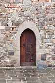 stock photo of rock carving  - A medieval wooden door with metal accents and a metal lock framed by carved rocks in a rock and brick wall of a castle interior - JPG