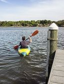 image of bayou  - Back view of a man in a small kayak rowing out from the pier - JPG