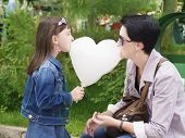 stock photo of candy cotton  - Mother and daughter eating cotton candy in the shape of heart - JPG