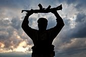 stock photo of terrorism  - Silhouette of muslim militant with rifle - JPG