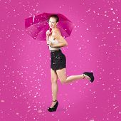 image of dancing rain  - Dashing retro pinup girl popping up one leg with umbrealla when doing a rain dance in fifties fashion - JPG