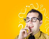 stock photo of riddles  - Inquisitive dorky male troubleshooting problem when thinking with look of discovery - JPG