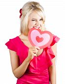 stock photo of heartbreaking  - A delicious young blonde woman winking while biting into a cardboard heart - JPG
