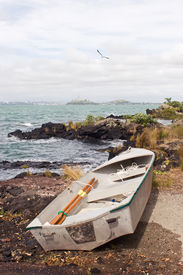 picture of scoria  - A dinghy rests on the shore of Rangitoto Island in the Hauraki Gulf of New Zealand - JPG
