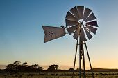 stock photo of early morning  - Farm windmill in clear early morning light - JPG