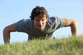 picture of intensive care  - Close up of a man doing pushups on the grass with the horizon in the background - JPG