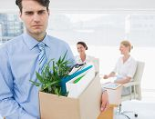 stock photo of forlorn  - Portrait of a young businessman leaving office with his belongings and colleagues in background - JPG