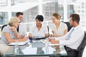 image of half-dressed  - Young well dressed business people in discussion at a bright office - JPG