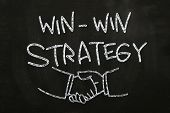 picture of negotiating  - Win Win Strategy quotes and hand shakes drawn with Chalk on Blackboard - JPG