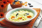 image of prunes  - Millet porridge with dried apricots and prunes in a bowl - JPG