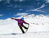 stock photo of snowboarding  - Snowboarder in mountains taking for the edge snowboard against the blue sky and clouds - JPG