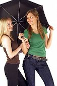Two attractive young women using an umbrella. All  on white background.