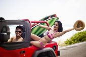 stock photo of sea-scape  - Young adventurous couple ready to surf at the beach with a red car - JPG
