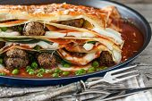 picture of lasagna  - Closeup of lasagna made with meatballs mozzarella cheese parmesan basil green peas and tomato sauce - JPG