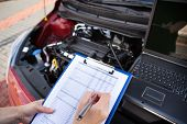 stock photo of clipboard  - Male Mechanic Writing On Clipboard While Examining Car Engine - JPG