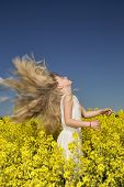 stock photo of rape  - Young girl with Long Hair on a Rape Field - JPG