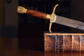 stock photo of sword  - 150 Year Old Bible With Sword on Top - JPG