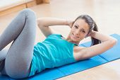 image of flat stomach  - Attractive woman doing abs workout at gym for muscle toning and flat stomach - JPG