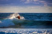 stock photo of scum  - Aerial reverse trick of a bodyboarder with backlight and scum