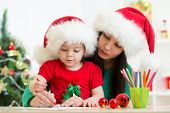 foto of letters to santa claus  - child girl and mother writing christmas letter to Santa Claus - JPG