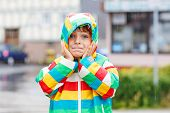 stock photo of rainy season  - Funny smiling little boy walking in city through rain wearing colorful rain coat and green boots outdoors at rainy day - JPG
