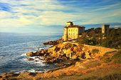stock photo of yellow castle  - Boccale castle landmark on cliff rock and sea on warm sunset - JPG