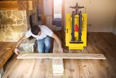 foto of overhauling  - Young handyman installing and measuring plywood for wooden floor - JPG