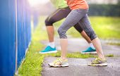 foto of rainy weather  - Young couple stretching after the run on asphalt in rainy weather - JPG