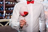 foto of wine cellar  - Sommelier kneading wine in the wine glass in the wine cellar - JPG