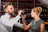 pic of wine cellar  - Romantic well-dressed couple drinking wine at the cellar